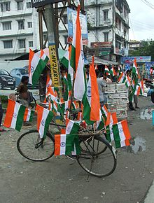 Several flags mounted on a bicycle parked on a road.