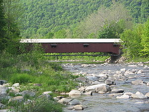 A red, wooden covered bridge over a rocky stream with a forest-covered mountain in the background