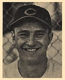 "A smiling man in a dark baseball cap with a ""C"" on the center."