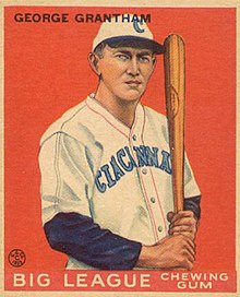 "A baseball card of a man holding a bat upright and leaning on his shoulder in a white baseball uniform with ""Cincinnati"" written on the chest."