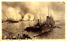 A fleet of warships lined up in a harbour with thick clouds of smoke coming out of their funnels