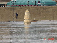 "Water from a river completely surrounds a stone obelisk. In the background are several people with news cameras. A building with a green roof is seen behind them. At the bottom right of the image is the camera's time: ""6 7:59 am""."