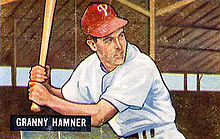 "A baseball card image of a man holding a baseball bat over his right shoulder; he is wearing a white baseball jersey and red baseball cap with a white ""P"" on the front"