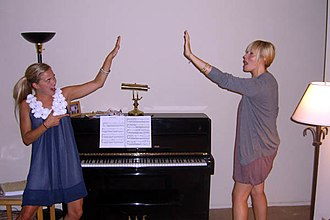 High five - Two women engaging in an air five (With finger-gun).
