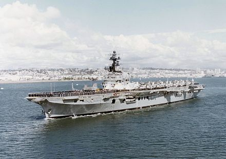 Colour photo of an aircraft carrier underway. Black-uniformed personnel line the perimeter of the flight deck, and a large number of aircraft with wings folded over sit on the deck.
