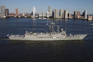 "A frigate with the number ""03"" painted near the bow. The ship is travelling slowly, and white-uniformed people line the decks with a city skyline in the background."
