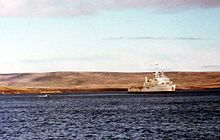 A warship at anchor. In the background is a flat, treeless landscape.