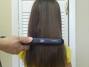 English: Example:hair being straighten with a regular curly iron..