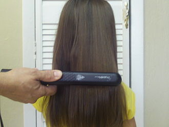 Hair straightening - Hair being straightened with a hair iron.