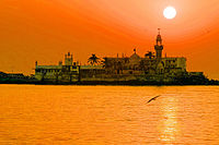 Photo: The Haji Ali Dargah, built in 1431, in the Mahim Bay can be reached from Mahalaxmi by a narrow causeway, and that only at high tide, when it is above the sea. A handsome example of Indian Islamic architecture, associated with legends about doomed lovers, the dargah contains the tomb of Saint Haji Ali. It sits 500 yards off the coast in the waters of Mahim Bay, near the neighborhood of Worli. It is connected with the Mahalaxmi Temple via a small path that goes into the sea, only accessible during low tide.