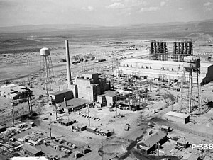 An aerial view of the Hanford B-Reactor site from June 1944. At center is the reactor building. Small trucks dot the landscape and give a sense of scale. Two large water towers loom above the plant.