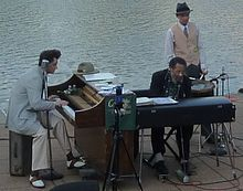 At left man in his thirties plays piano, man in the middle is in his seventies also playing piano, man at right in his twenties or thirties playing a snare drum. On the Mississippi waterfront