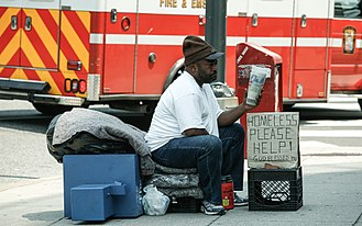 "Poverty in the United States - Homeless man with sign that says ""Please help"""