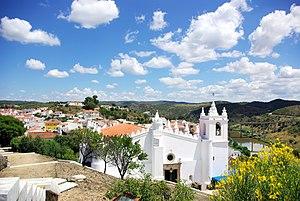 Church of Nossa Senhora da Anunciação - A view of the church on the hilltop with the skyline of Mértola