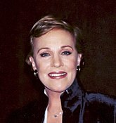 A Caucasian female with gold earrings, blue eyes, and a necklace in a navy blue outfit. She is standing against a black backdrop.