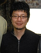 A photograph of a Japanese man wearing glasses.