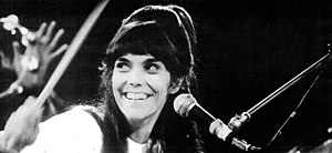 Black and white photograph of Karen Carpenter drumming on stage