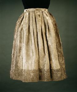 Bukser til Karl XI:s Strumpebandsordensdräkt, England 1669.   Vida kjolelignende bukser af rhingravetyp af hvidt blomeret sølvdug - hvidt sideanatlas med indvævede blomster.   Livrustkammaren, Stockholm