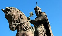A stone statue of a man in warrior clothes on horseback.