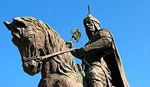 Каменная статуя человека в воине одежду верхом.