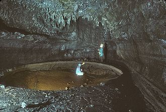 Kazumura Cave - Collapse into a round lava lake after it drained. The source of the lava is the lavafall in the background.