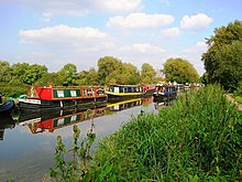 A canal passing through countryside. Numerous narrowboats are moored on the far bank, and a narrowboat is travelling upstream towards the foreground.