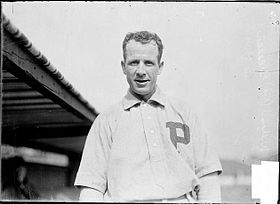 "A smiling dark-haired man in a white baseball jersey with a block ""P"" over the left breast"