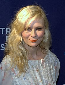 Kirsten Dunst is pictured outdoors; she has wavy red hair and is wearing a white dress with ruffles around the collar and in front
