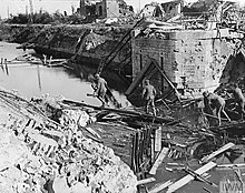 The remaining column of a destroyed bridge, with surrounding rubble that has partially blocked the flow of the canal. Members of the 2/5LF walk across some of the rubble.