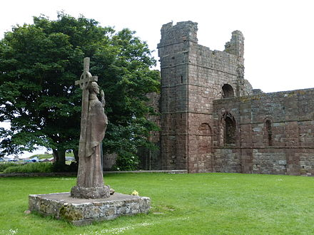 Modern statue of St Aidan beside the ruins of the mediaeval priory Lindisfarne Priory ruins and St. Aidan statue.jpg