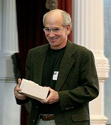 Sachar shown from the waist up, smiling, and holding a small box.