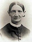 antiga fotografia em sépia de Lucy Smith Millikin, tirada entre 1850 e 1900. A mulher mais velha tem cabelos bem puxados, orelhas proeminentes e ombros delgados.  Ela está vestida com um vestido escuro com gola branca.