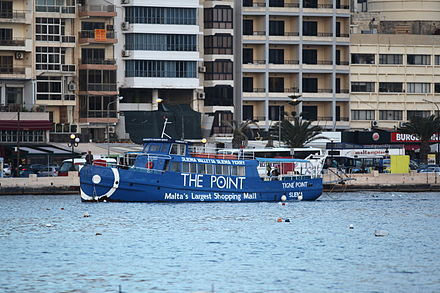 The ferry boat Cominotto with an advert for The Point Shopping Mall. Malta - Sliema - Triq Ix-Xatt - Ferry (Triq Ix-Xatt (Gzira)) 01 ies.jpg