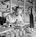 Man maakt thorarollen achter een volle werktafel, Bestanddeelnr 255-2343.jpg