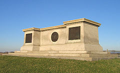 A large monument of off-white stone. Its shape resembles a long, flat pedestal. It sits atop a grassy knoll with a bright blue sky overhead.