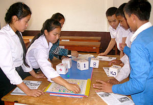 "Numeracy - Children in Laos have fun as they improve numeracy with ""Number Bingo."" They roll three dice, construct an equation from the numbers to produce a new number, then cover that number on the board, trying to get 4 in a row."