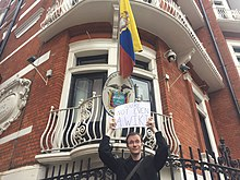 "Garrett in 2016, standing outside the Ecuadorian Embassy in London, where WikiLeaks founder Julian Assange had received asylum, holding a sign saying ""You're not even a Wiki"""