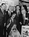 Mayor Robert Wagner, Senator Herbert Lehman, Governor Nelson Rockefeller, ILGWU President David Dubinsky, and others watch as Mrs. Mary Rockefeller sews an ILGWU union label into a garment. (5279330371).jpg