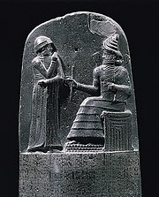 King Hammurabi is revealed the code of laws by the Mesopotamian sun god Shamash.
