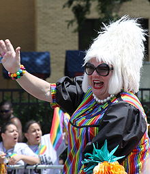 Miss Foozie waves during a pride parade.