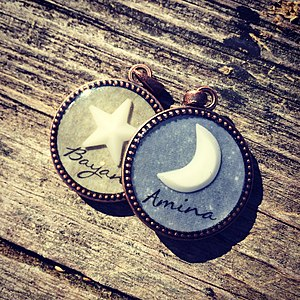 Breast milk jewelry - Bezel set breast milk pendants, one with a breast milk crescent, one with a star with custom colored backgrounds and names.