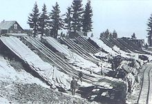 Men working next to chords of wood at the bottom of wooden ramps on the side of a hill. A building and set of trees is on top of the hill. A rail line parallels the chords of wood.