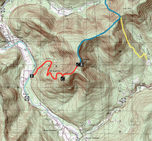 A topographic map with brown contour lines on a green and white background with red, blue and yellow routes overlaid along with black and white icons. Three roads alongside the edge of the map have signs with the numbers 28, 212 and 214.