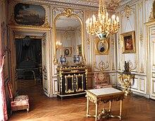 Pièce comportant des boiseries blanches et dorées, parquet au sol et lustre doré, une porte à gauche surmonté d'un tableau, un bahut de couleur noire surmonté d'un miroir et plusieurs portraits peints aux murs