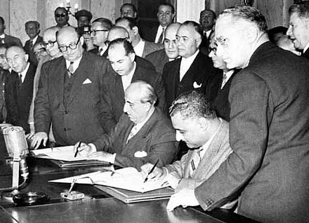 Egyptian president Gamal Abdel Nasser (seated right) and Syrian president Shukri al-Quwatli sign the accord to form the United Arab Republic in 1958. The short-lived political union briefly represented both states and was used as the name of Egypt following Syria's withdrawal in 1961. NasserQuwatliUAR.jpg