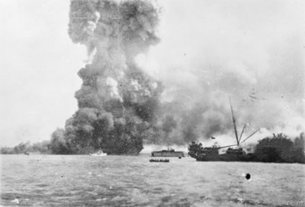 MV Neptuna explodes at Stokes Hill Wharf. In front of the explosion is HMAS Vigilant which is undertaking rescue work. In the centre background is the floating dry dock holding the corvette HMAS Katoomba. In the foreground is the damaged SS Zealandia. Neptuna explosion 19 February 1942.jpg