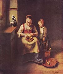 Young woman grating carrots, with a child watching