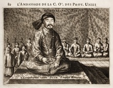 Black-and-white print of a man with small eyes and a thin mustache wearing a robe, a fur hat, and a necklace made with round beads, sitting cross-legged on a three-level platform covered with a rug. Behind him and much smaller are eight men (four on each side) sitting in the same position wearing robes and round caps, as well as four standing men with similar garb (on the left).