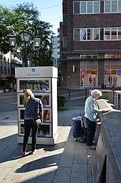Browsing A Public Bookcase In Essen