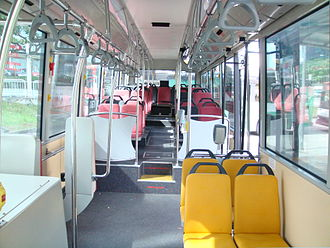 Transit bus - Interior of a wheelchair-accessible transit bus, with bucket seats and smart-card readers at the exit.